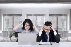 Frustrerade entreprenörer som ser bärbara datorn Arkivbild