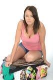 Frustrerade Fed Up Unhappy Young Woman som försöker att stänga en flödande över resväska, genom att sitta på den Arkivbild