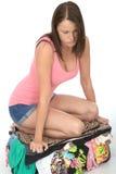 Frustrerade Fed Up Young Woman Trying som stänger en flödande över resväska, genom att knäfalla på den Royaltyfri Fotografi
