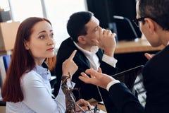 Frustrerade rödhåriga kvinnapunkter fingrar på den vuxna mannen, som vände till annan väg, på kontoret för advokat` s arkivbilder