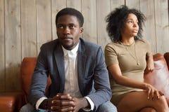 Frustrerade upprivna afrikanska par grälar in samtal inte efter fikonträd Arkivbild
