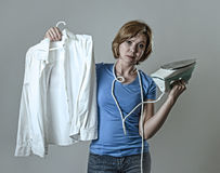 Frustrerade uttråkad för kvinna eller för hemmafru ledsen och stressad hållande vit skjorta och järn som är ilskna och Arkivfoton