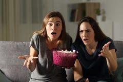 Frustrerade vänner som håller ögonen på tv i natten Arkivbild