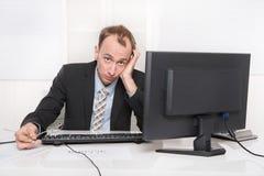 Frustrerat anställdsammanträde och skrivbord som rymmer hans huvud - problem arkivfoto