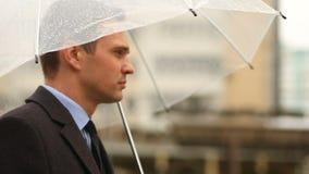 Frustrerat av vädret som står under paraplyet under regnet Olycklig man i en dräkt stock video