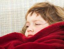 Frustrerat barn som ligger på soffan royaltyfri foto