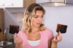 Frustrerat bränt rostat bröd för ung kvinna innehav royaltyfri fotografi