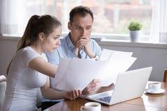 Frustrerat gift par som hemma kontrollerar räkningar royaltyfri fotografi