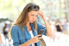 Frustrerat innehåll för kvinnaläsningtelefon i gatan arkivfoto