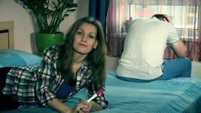 Frustrerat kvinna- och mansammanträde på säng i sovrum efter graviditetstestresultat arkivfilmer