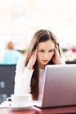 Frustrerat kvinnaarbete på henne bärbar dator royaltyfria foton