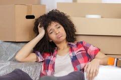 Frustrerat kvinnasammanträde vid kartonger i nytt hus fotografering för bildbyråer