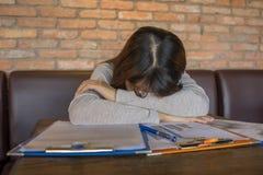 Frustrerat kvinnligt sova på många försäljningsrapporter royaltyfri fotografi