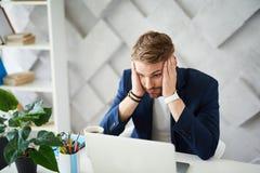 Frustrerat mansammanträde på mitten för bärbar dator i regeringsställning arkivfoton
