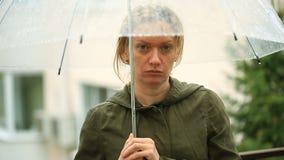 Frustrerat med väder som står under paraplyet under regn olycklig kvinna lager videofilmer