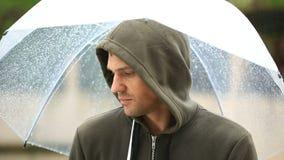 Frustrerat med väder som står under paraplyet under regn olycklig man lager videofilmer
