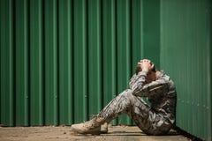 Frustrerat militärt soldatsammanträde med händer på huvudet royaltyfria bilder