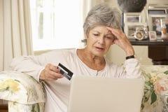 Frustrerat pensionerat högt kvinnasammanträde på Sofa At Home Using Laptop royaltyfri foto