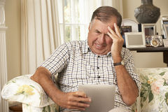 Frustrerat pensionerat sammanträde för hög man på den Sofa At Home Using Digital minnestavlan royaltyfri bild