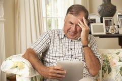 Frustrerat pensionerat sammanträde för hög man på den Sofa At Home Using Digital minnestavlan royaltyfri foto
