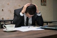 Frustrerat stressat asiatiskt affärsmansammanträde i coffee shopintelligens royaltyfri foto