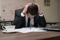 Frustrerat stressat asiatiskt affärsmansammanträde i coffee shopintelligens arkivfoton