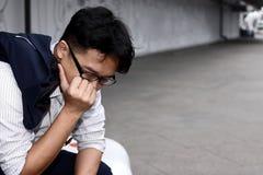 Frustrerat stressat ungt asiatiskt lidande för affärsman från strängt problem arkivbild