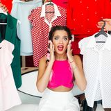 Frustreted brunette in pink having a problem of choosing clothes. Crop, closeup portrait of young girl in pink blouse waching on camera and holding hands stock images