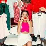 Frustreted brunette in pink having a problem of choosing clothes. Crop, closeup portrait of young girl in pink blouse waching on camera and holding hands stock photography
