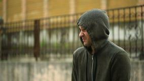 Frustriert durch das Wetter, stehend im Regen Der unglückliche Mann stock footage