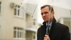 Frustriert durch das Wetter, stehend unter dem Regenschirm während des Regens Unglücklicher Mann in einer Klage stock video footage