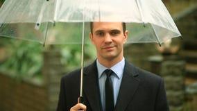 Frustriert durch das Wetter, stehend unter dem Regenschirm während des Regens Unglücklicher Mann in einer Klage stock footage