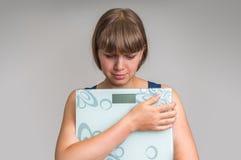 Frustrierte überladene Frau mit Skalen lizenzfreie stockfotos
