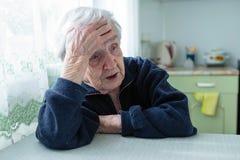 Frustrierte alte Frau, die zu Hause am Tisch sitzt lizenzfreie stockfotos