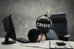 Frustrierte Arbeitskraft mit Krisenwort auf Bombe lizenzfreie stockfotos