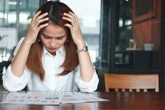 Frustrierte betonte junge asiatische Geschäftsfrau, die Schreibarbeit oder Diagramme an Arbeitsplatz analysiert Denken und durchd stockfotografie