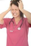 Frustrierte betonte verärgerte schöne junge Ärztin Pulling Her Hair Stockfotografie
