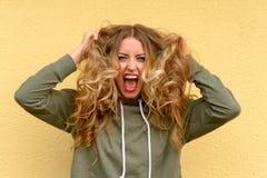 Frustrierte blonde Frau, die an ihrem langen Haar zerreißt Lizenzfreies Stockfoto