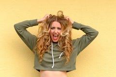 Frustrierte blonde Frau, die an ihrem langen Haar zerreißt Lizenzfreie Stockfotos