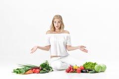 Frustrierte blonde Frau verbreitet Hände in beiden Richtungen und in vielen Frischgemüse auf weißem Hintergrund Stockbild