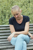 Frustrierte Blondine sitzen auf der Bank Lizenzfreies Stockfoto