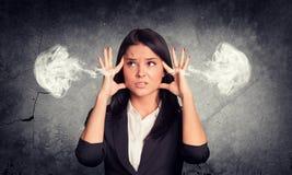 Frustrierte Frau, die Finger zu seinem Tempel hält Stockfotografie
