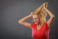 Frustrierte Frau, die ihr schädigendes blondes Haar hält Stockfotos