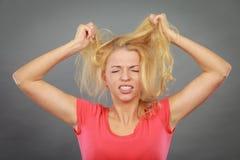 Frustrierte Frau, die ihr schädigendes blondes Haar hält Stockfoto