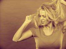 Frustrierte Frau, die ihr schädigendes blondes Haar hält Stockfotografie