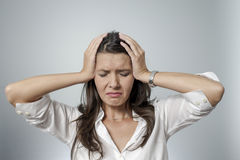Frustrierte Frau, die ihren Kopf zwischen ihren Händen nimmt Stockbilder