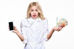 Frustrierte Frau, die Schultern zuckt, Handyleeren bildschirm zeigt und Lasten von Eurobanknoten auf weißem Hintergrund hält stockfotos