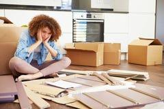 Frustrierte Frau, die Selbstbau-Möbel zusammenfügt Stockbilder