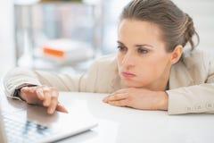 Frustrierte Geschäftsfrau, die mit Laptop arbeitet