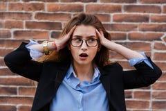 Frustrierte Geschäftsfrau, die seine Hände zu ihrem Kopf in der Frustration hält lizenzfreies stockfoto
